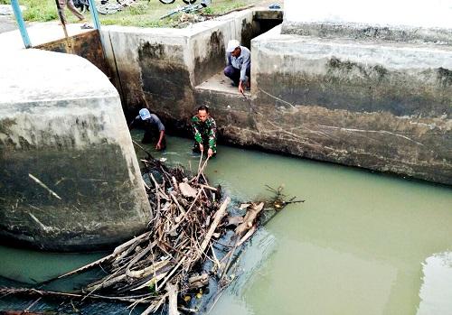 Tanpa Ragu, Babinsa Ini Terjun Langsung Bersihkan Tumpukan Sampah di Pintu Air