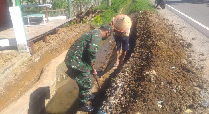 Peduli Kebersihan Lingkungan Sekitar, Babinsa Bantu Warga Bersihkan Parit Jalan