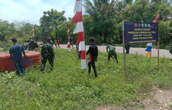 Personel Satgas TMMD bersama Masyarakat Bergotong Royong Bersihkan Lahan Pembuatan Lapangan Volly