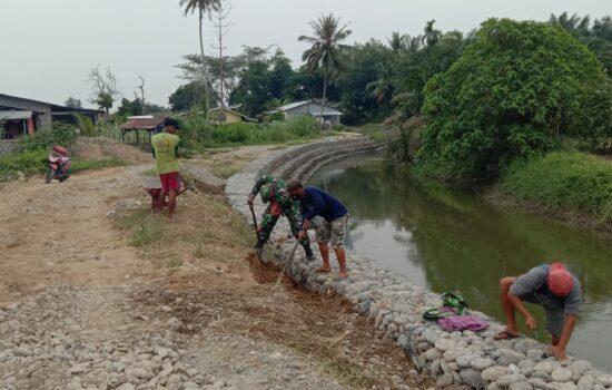 Antisipasi Banjir ke Perumahan Warga, Babinsa Bantu Warga Pasang Bronjong